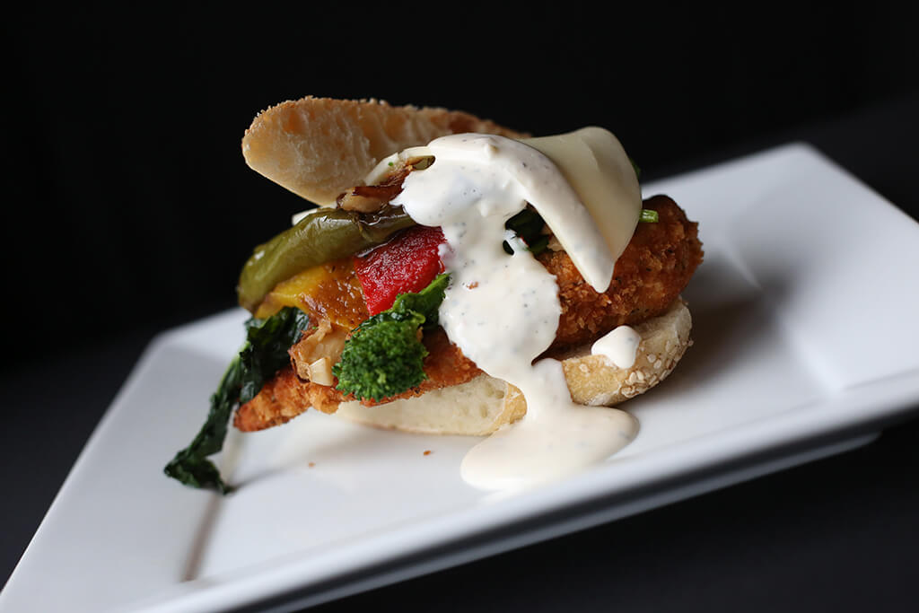 fried chiken sandwich with roated vegetables and savory sauce